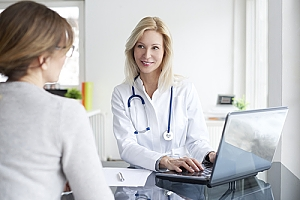 Doctor at computer talking to young woman