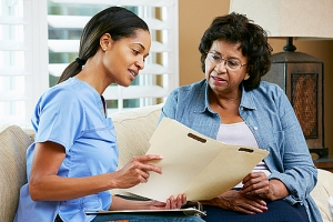 Nurse holding folder and discussing with senior woman