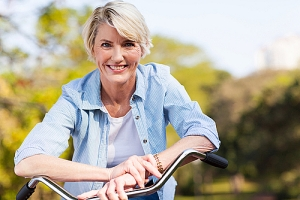 Senior woman in blue blouse on bike smiling