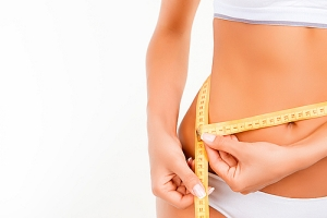 Woman using measuring tape on stomach and waist