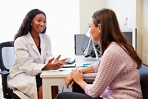 Young woman having consultation with doctor sitting at desk