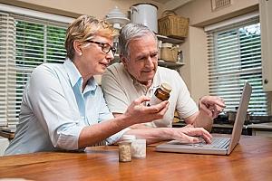Senior couple researching prescriptions online telehealth