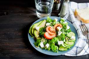 Fresh green salad and glass of water on a table. Eat a light meal or a snack before your appointment for IUD Insertion