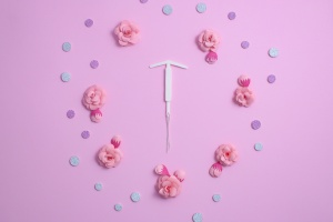 IUD placed around flowers on a pink background