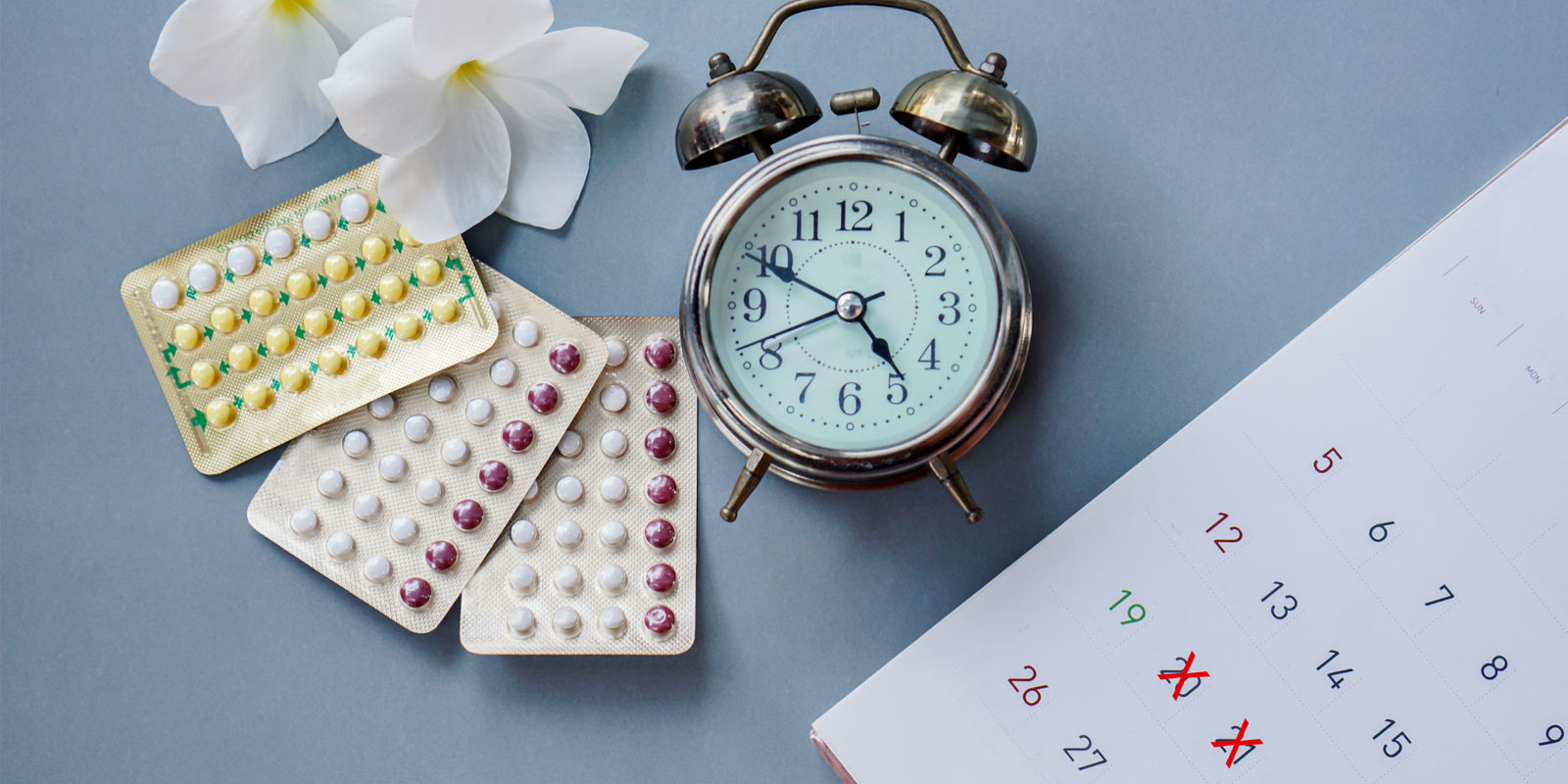 hormonal contraceptive pills next to a clock and calendar