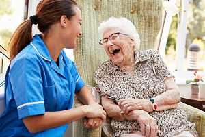 Nurse attending a Senior Woman Sitting In Chair