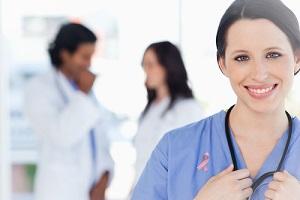 nurse standing wearing breast cancer awareness ribbon