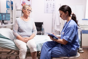 Nurse Practitioner writing prescription on clipboard discussing with senior man