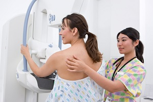 professional radiologist helping and attending a patient on a mammogram machine for breast care
