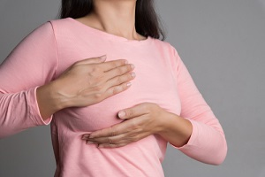 woman hand checking lumps on her breast for signs of breast cancer for breast care