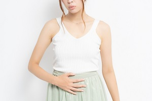young woman putting her hand on her stomach because of Menstrual Disorders